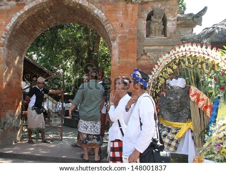 DENPASAR, INDONESIA - MAY 13:  Balinese men guarding the entrance to the Royal Temple and on-lookers before the Royal Ngaben or cremation ceremony in Ubud, Denpasar, Bali, Indonesia on May 13, 2013.
