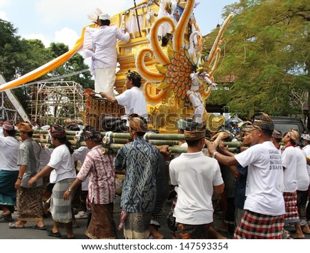 DENPASAR, INDONESIA - MAY 12:  Balinese men run around in circles with the pyre to ward off evil spirits in a Ngaben or cremation ceremony in Ubud, Denpasar, Bali, Indonesia on May 12, 2013.