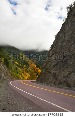 Dense autumn clouds above mountain northern road