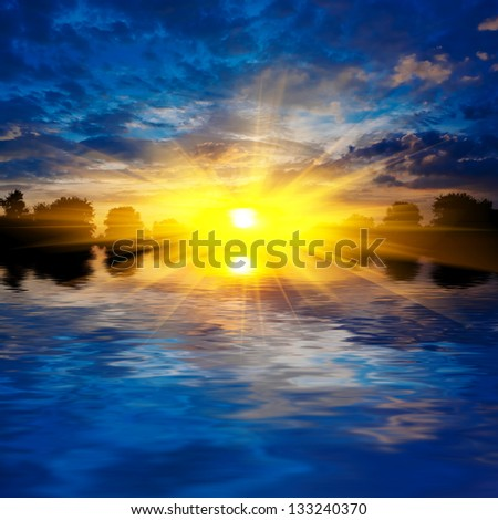 dense clouds dramatic sunset over a lake - stock photo