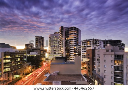Dense development with modern contemporary skyscrapers in St Leonards suburb of Sydney, Australia. Sunset illuminates windows and streets with blurred traffic