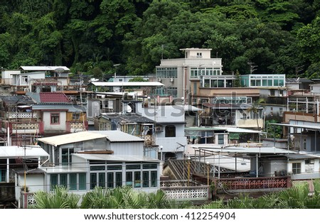 Densely built traditional village houses in Tai Po, Hong Kong. Expensive and overcrowded housing conditions are prevalent in Hong Kong. - stock photo