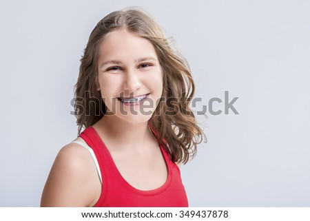 Dental and Medical Concept. Smiling Caucasian Young Blond Teenage Girl With Teeth Bracket System. Against White Background.Horizontal Image - stock photo