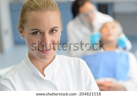 Dental assistant closeup looking camera professional dentist checkup patient woman - stock photo