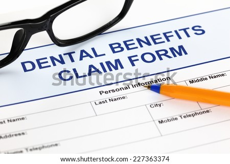 Dental benefits claim form with glasses and ballpoint pen.  - stock photo