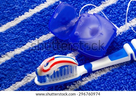 Dental floss and a blue toothbrush on a towel.  Saturated, vivid image