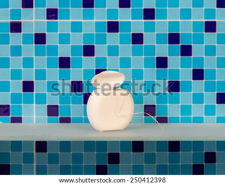Dental floss in bathroom on a blue background - stock photo
