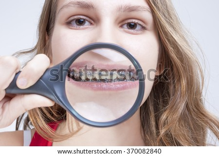 Dental Health and Hygiene Concepts. Caucasian Female Demonstrating Her Teeth with Brackets Through Magnifying Glass. Horizontal Image