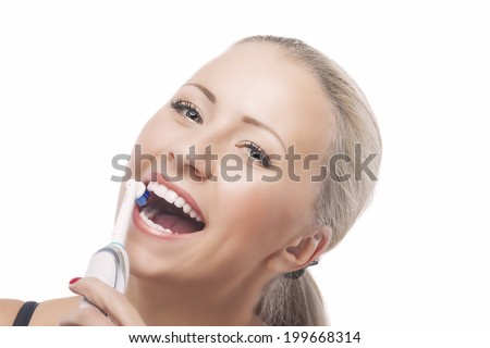 Dental Health: Blond Caucasian Woman Brushing Her Teeth with Electric Toothbrush. Isolated Over Pure White Background. Horizontal Image Composition - stock photo