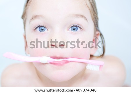 Dental hygiene. Close up of little blond girl brushing her teeth. Fun in the bath - stock photo