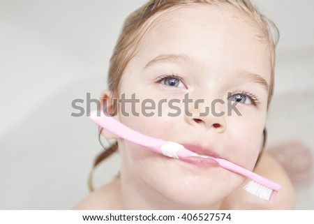 Dental hygiene. Close up of little girl brushing her teeth. Fun in the bath - stock photo