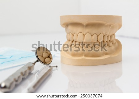 Dental mold showing the teeth of the upper and lower jaw with dental tools and a face mask on a wooden table in a dental care and examination concept - stock photo