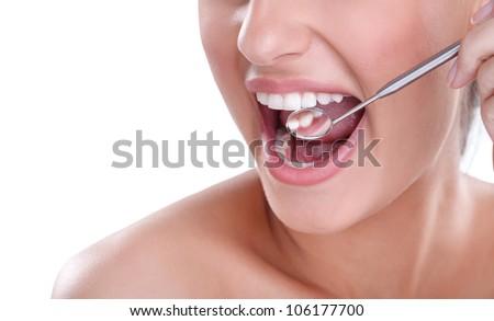 dental mouth mirror near healthy white woman teeth - stock photo
