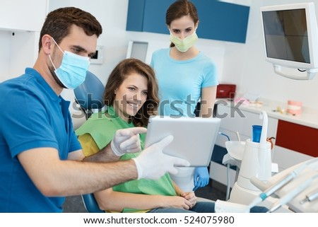 Dental team and patient at dentist's surgery.