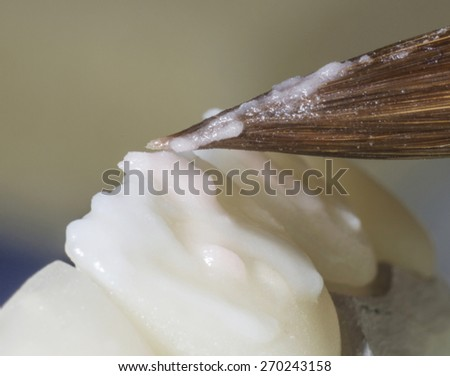 Dental technician applied glaze on ceramic crown - stock photo