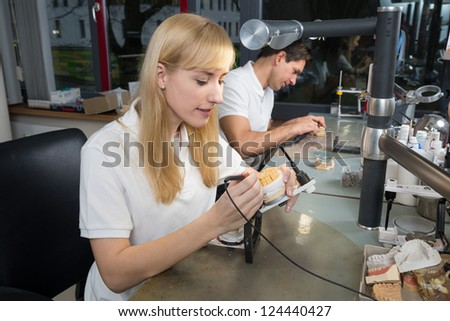 Dental technician applying wax to a prosthesis model in an articulator
