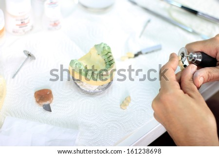 dental technician processes the artificial teeth with micromotor - stock photo