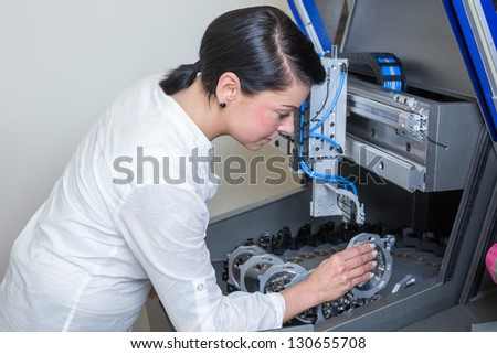 Dental technician working on a milling machine