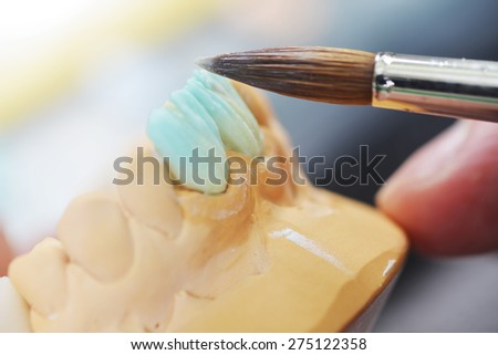 dental technician working on false teeth. table with dental tools.  - stock photo