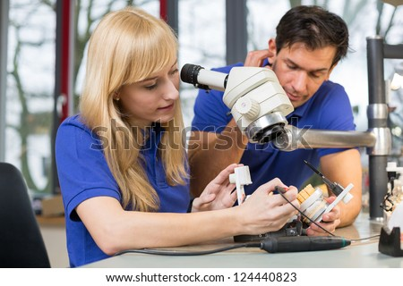 Dental technicians working on mold under a microscope in a lab