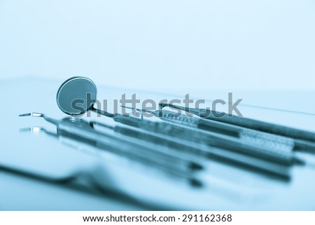 Dental tools and equipment over blue background.Set of metal medical equipment tools for teeth dental care - stock photo