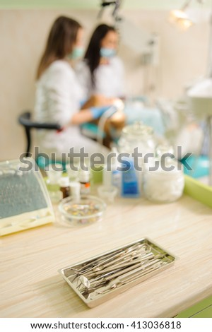 Dental tools on foreground and female dentist with assistant treating teeth on the background. Medical equipment. Specialized equipment to treat all types of dental diseases in the office. - stock photo
