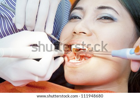 Dental treatment of young asian woman at the dentist office - stock photo