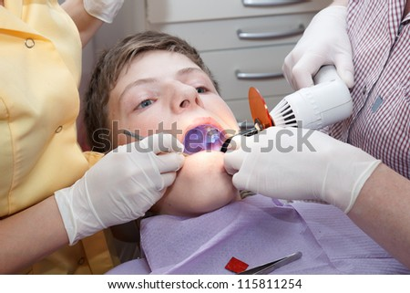 dental treatment with dental curing light - stock photo