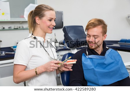 Dentist advising a patient about cleaning the teeth properly