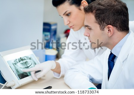 Dentist and assistant analyzing x-ray at the dental clinic - stock photo