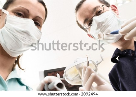 Dentist and assistant are examining you the patient - stock photo