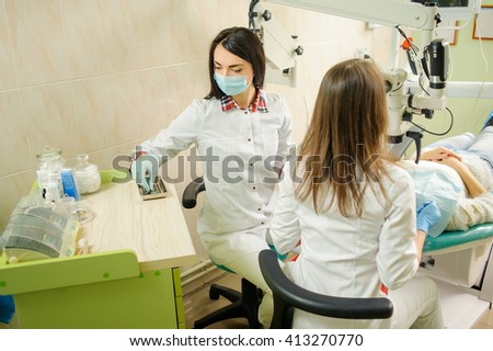 Dentist and assistant in a dental hospital, wearing masks and gloves. Beautiful woman dentist holding dental tools getting ready for treatment with microscope. Medical equipment - stock photo