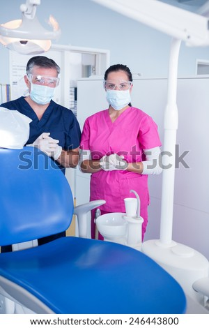 Dentist and assistant in surgical mask and protective glasses at the dental clinic - stock photo