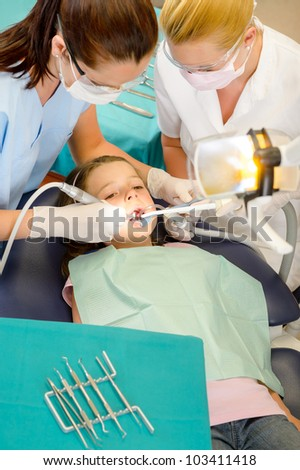 Dentist and assistant with little girl patient  at stomatology clinic - stock photo