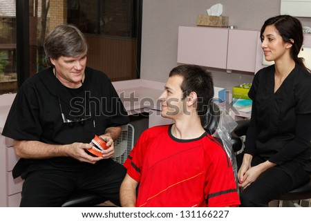 Dentist and his assistant talking with patient about dental care.