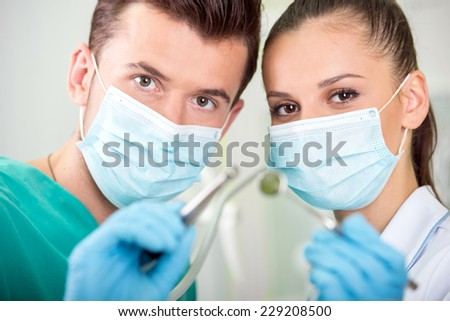 Dentist and his assistant with tools in dental clinic.
