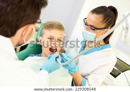 Dentist and nurse are curing a little boy patient. - stock photo