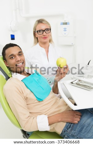 Dentist and teeth concepts. Portrait of young man sitting in the dentist's chair and holding an apple at the dentist's office. - stock photo