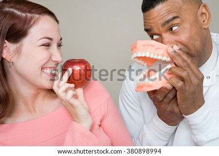 Dentist and woman holding an apple and false teeth - stock photo