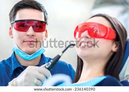 Dentist at work in the UV protective glasses. The dentist fixes the dental filling UV lamp while the patient is sitting in the dental chair and smiling widely.