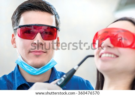 Dentist at work in the UV protective glasses. The dentist fixes the dental filling UV lamp while the patient is sitting in the dental chair and smiling broadly.