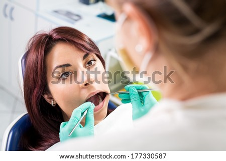 Dentist checking dental hygiene on patient in the office. Selective focus, focus on the patient.