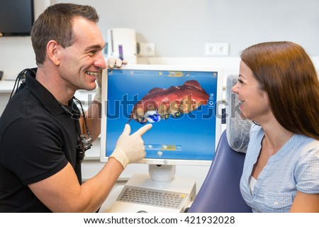Dentist counseling patient about CEREC (Chairside Economical Restoration of Esthetic Ceramics) dental technology