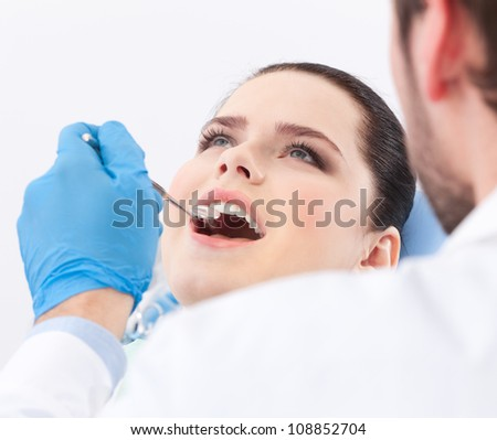 Dentist examines teeth of the patient on the dentist's chair - stock photo