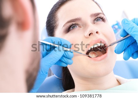 Dentist examines the teeth of the patient on the dentist's chair - stock photo