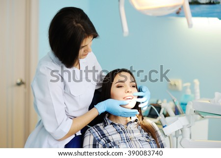 dentist examines the teeth to the patient. beautiful girl at the dentist