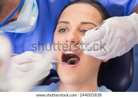 Dentist examining a patient with angle mirror and sickle probe in dental clinic - stock photo