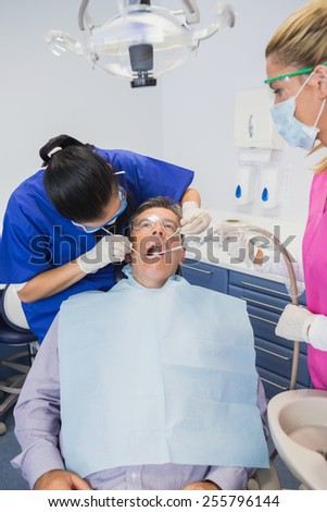 Dentist examining a patient with her dental nurse holding suction hose - stock photo