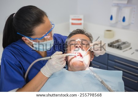Dentist examining a patient with tools and light in dental clinic - stock photo