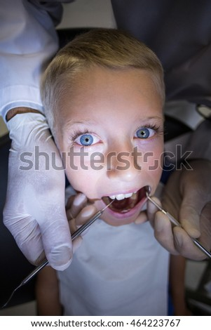 Dentist examining a young patient with tools at dental clinic